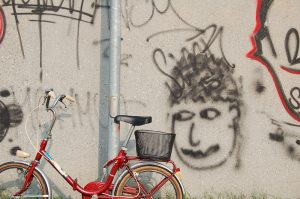 Fahrrad, das an einer Straßenlaterne steht. Im Hintergrund ist eine Hauswand voller Graffiti.