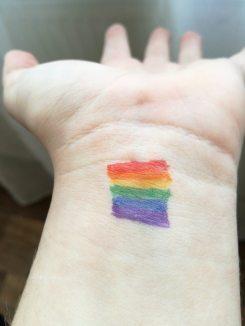 Ein Arm auf dessen Handgelenk die Regenbogenfahne aufgemalt wurde.